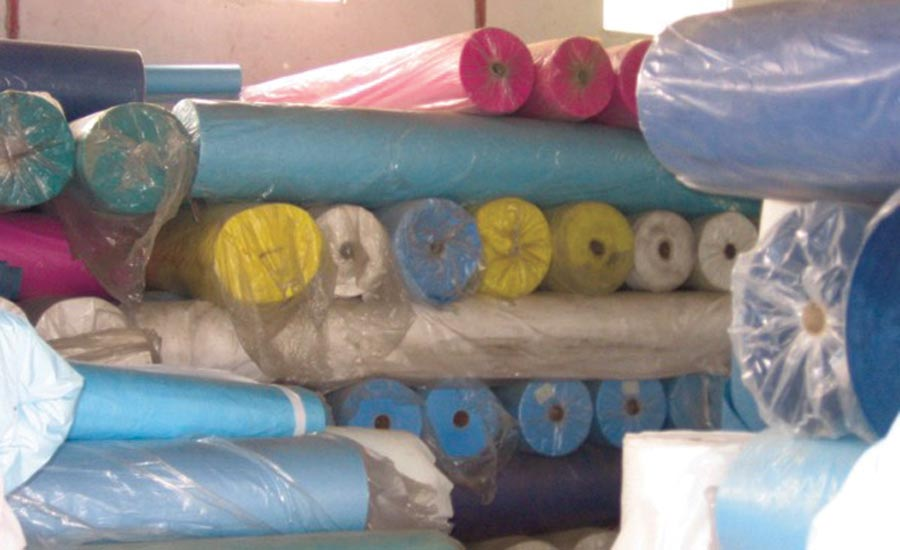 Rolls of various materials stacked in a factory in China to be converted into PPE.