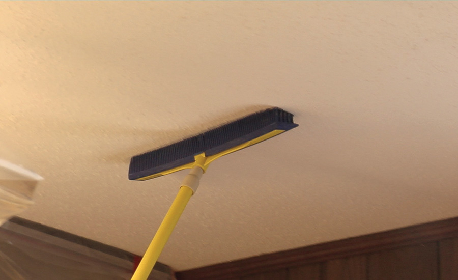 using a broom on the ceiling