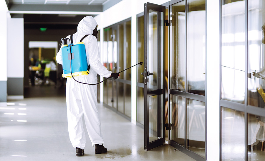 person in hazmat outfit spraying cleaner
