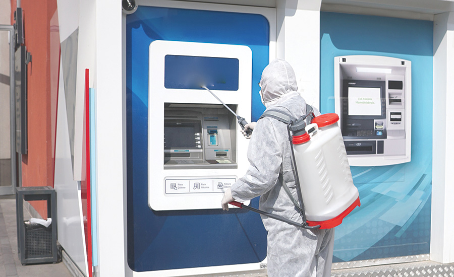 person in hazmat outfit cleaning an atm machine