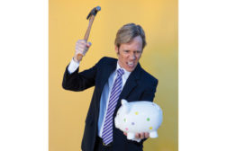 cross stock photo man breaking piggy bank